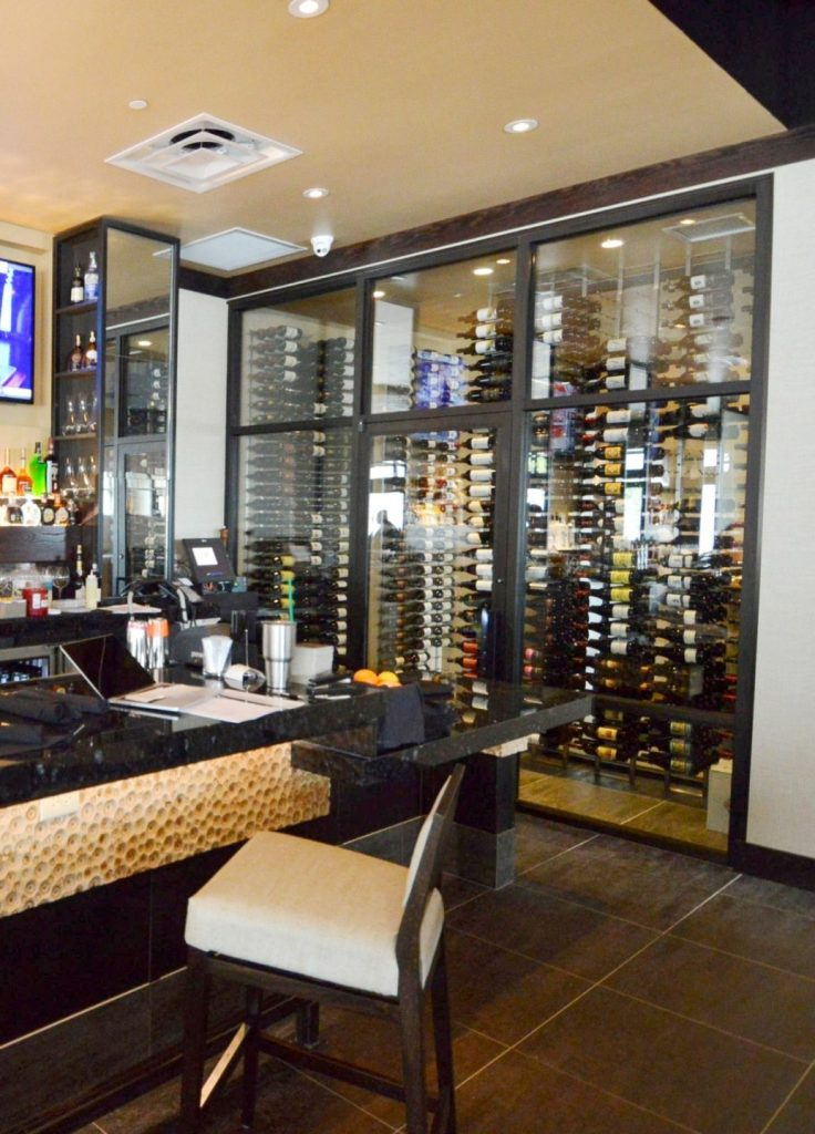 This contemporary commercial custom wine cellar in Miami, florida, displays the wines in metal wine racks.
